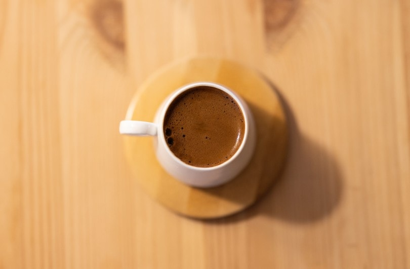 a cup of coffee on wooden table