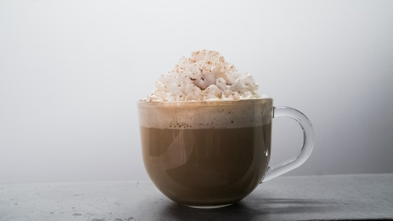 a glass of coffee with whipped cream