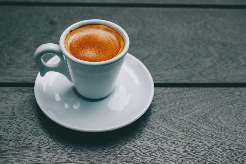 a white ceramic cup filled with coffee on saucer