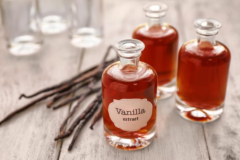 بطری های عصاره وانیل و دانه های وانیل خشک روی میز