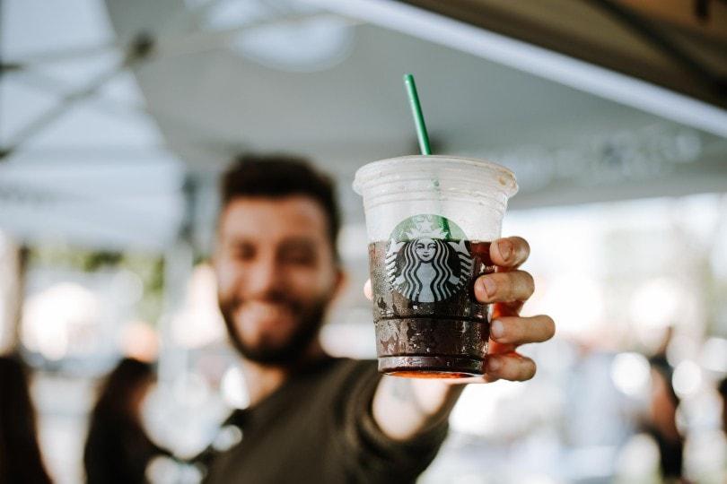 مردی که نوشیدنی استارباکس را در دست داشت