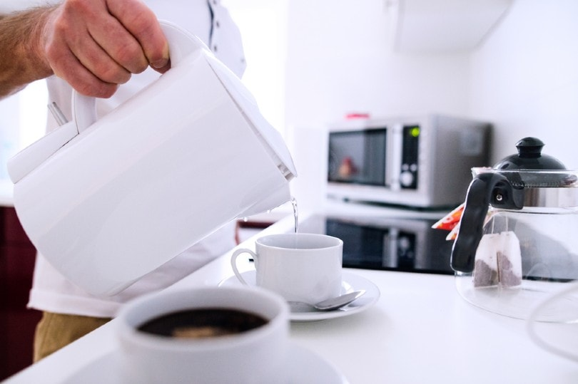 man pouring hot water from electric kettle to the cup