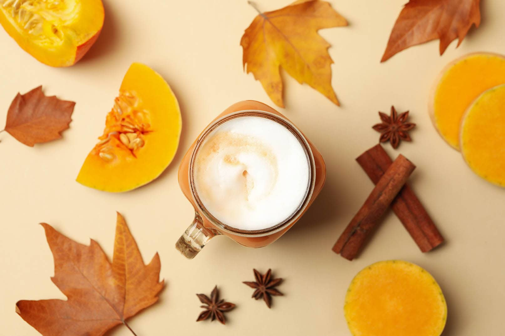 pumpkin spice latte surrounded with cinnamon and leaves