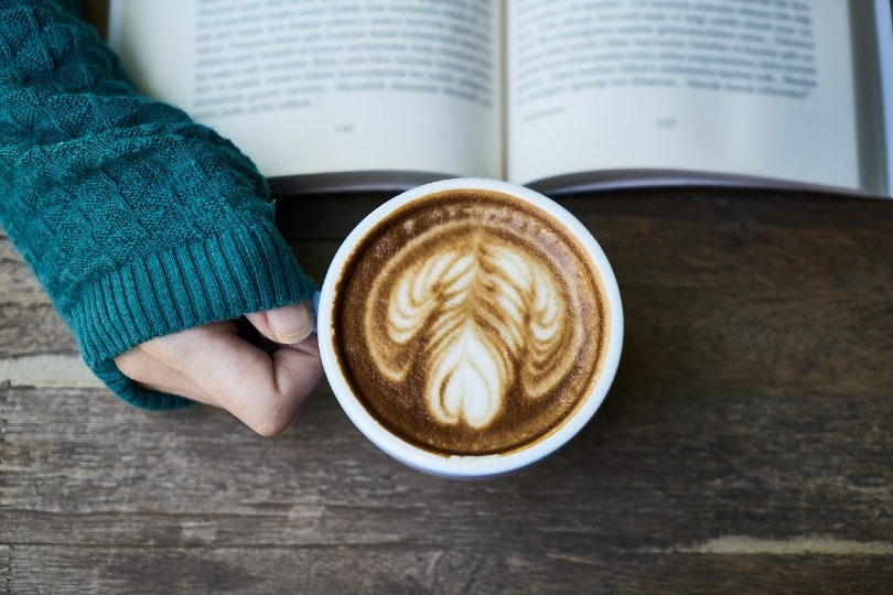 زنی که یک فنجان قهوه در دست دارد