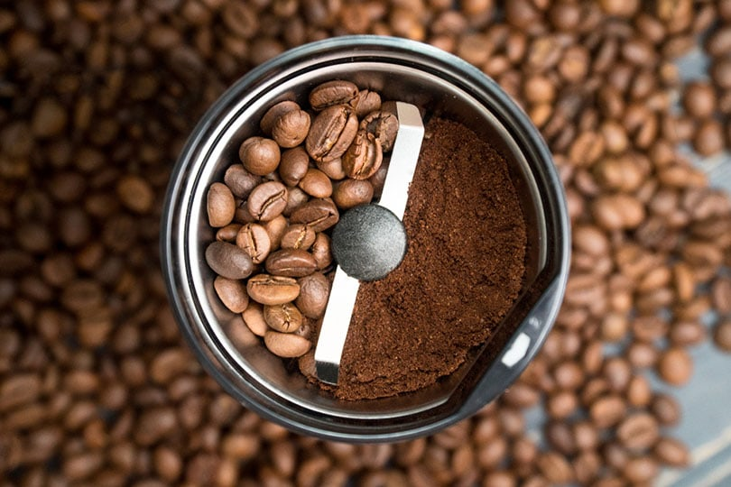 coffee grinder with coffee beans and ground coffee