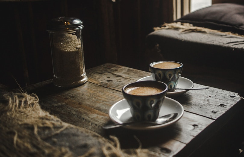cortado coffees in coffee cups on a wooden table in a cozy rustic Guatemalan café